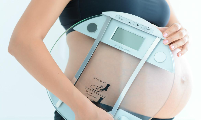 ganho de peso durante a gravidez. Gestante com balança