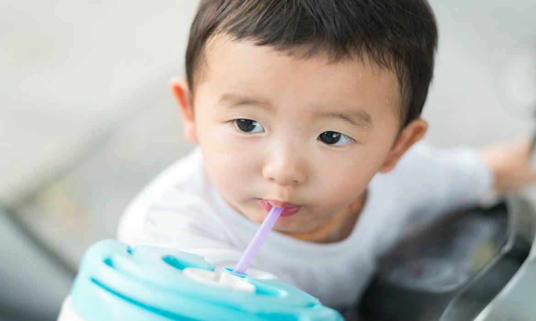 Menino bebendo água e mantendo a hidratação no verão